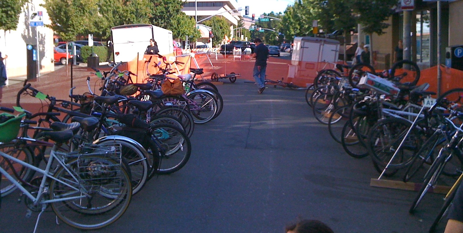Bicycles inside orange security fencing on kickstands and racks